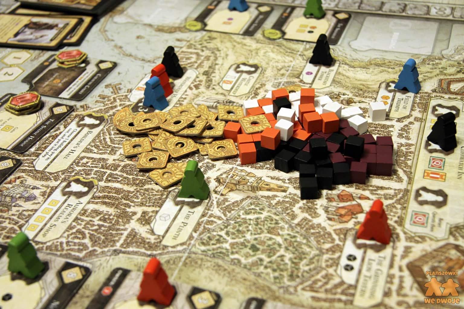 Plansza gry Lords of Waterdeep w trakcie rozgrywki z drewnianymi kostkami i żetonami na środku.